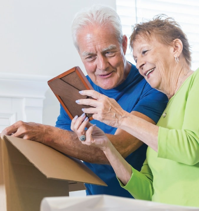 couple packing moving box looking at photo in frame