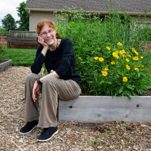 woman sitting on flower bed box